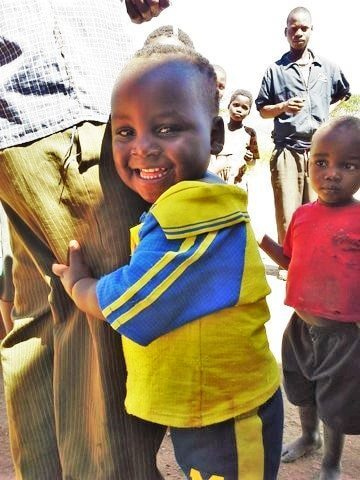cute Malawian boy holding his fathers leg and smiling from Project Kindy kindergarten